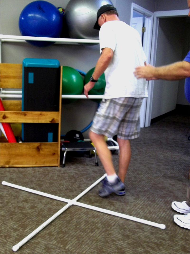 Patient Balancing and Stepping around 4 square equipment while Therapist behind and helping.