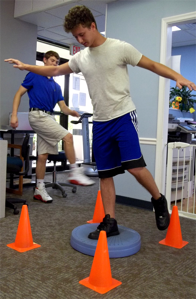 Young Man, Balancing one Foot on Soft Surface and Touch Toe to Orange Cone Behind Him. Three other Cones Place Around Him as well.