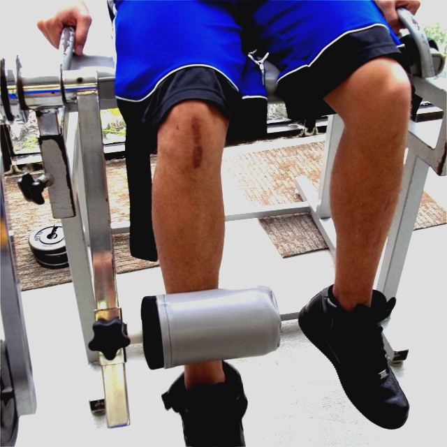 Man with Scar on Knee Using knee extension and ham string curl machine.
