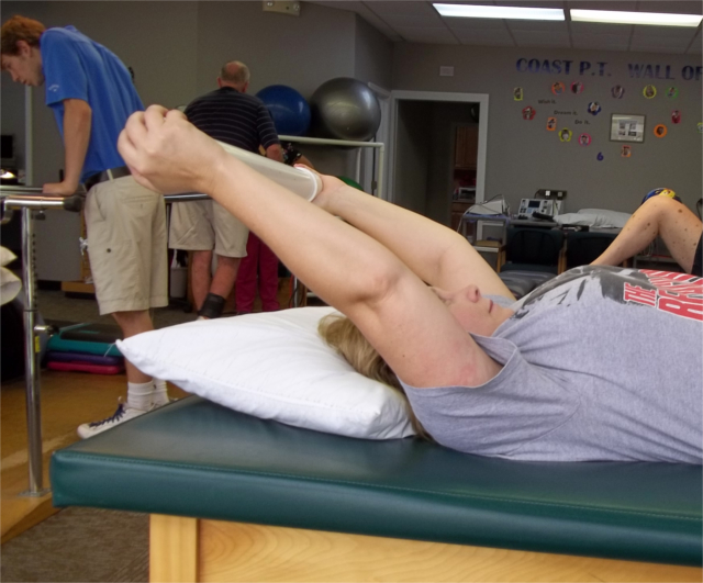 Patient laying on table, with arms stretched over head. Range of Motion after Surgery