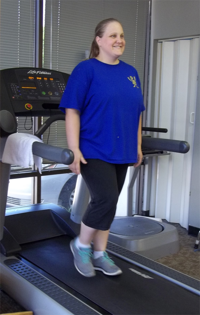 Woman Smiling while Walking Backwards on Treadmill